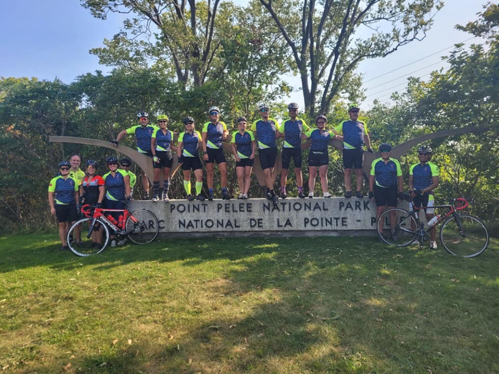 Paramedics and their bicycles at the entrance sign to Point Pelee National Park
