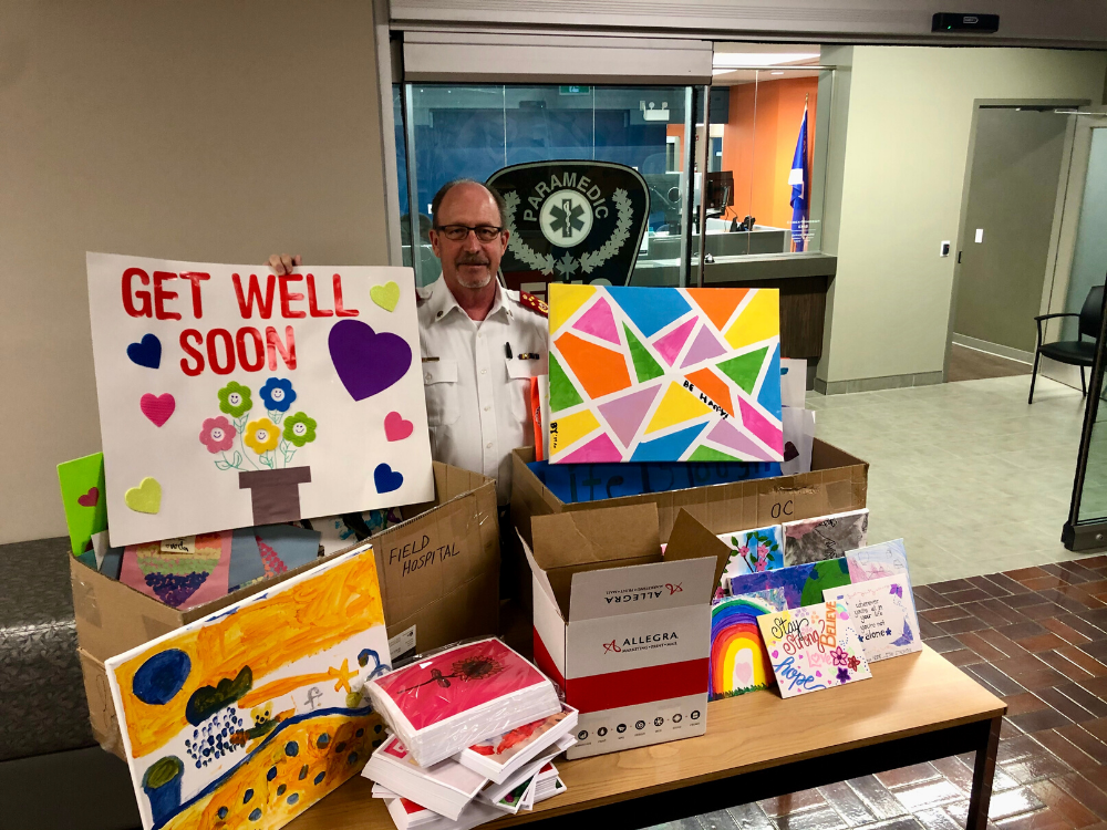 Essex-Windsor EMS Chief Bruce Krauter stands with inspirational art created by area kids.