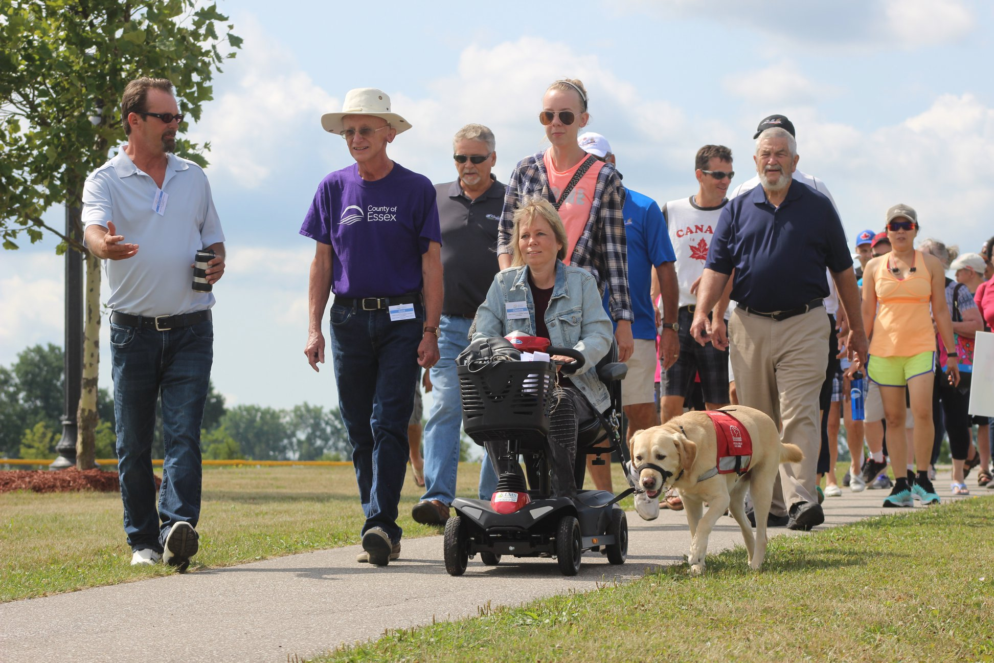 Participants walk and use a wheelchair with a service dog during the inaugural Celebrate Our Abilities Accessibility Awareness Walk in LaSalle.