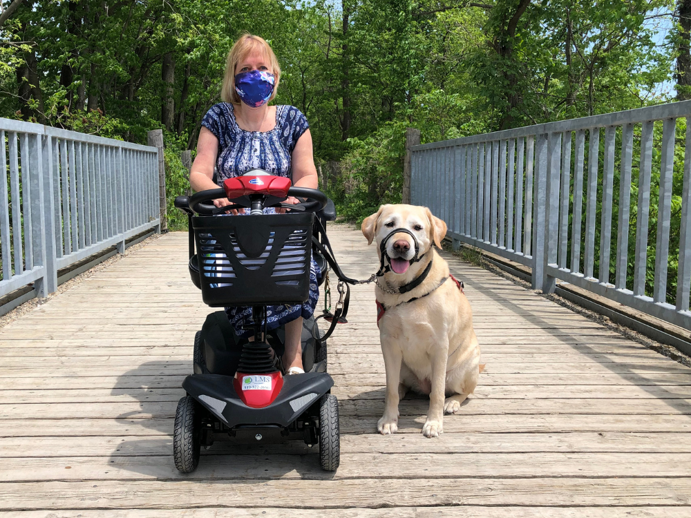 Christine Easterbrook a Greenway trail with her mobility scooter and dog