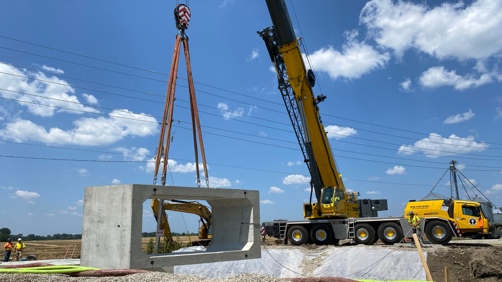 Concrete section of a new culvert is lowered into place on County Road 17.