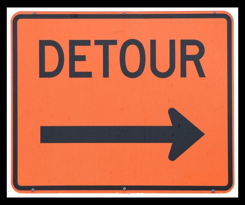 An orange Detour sign