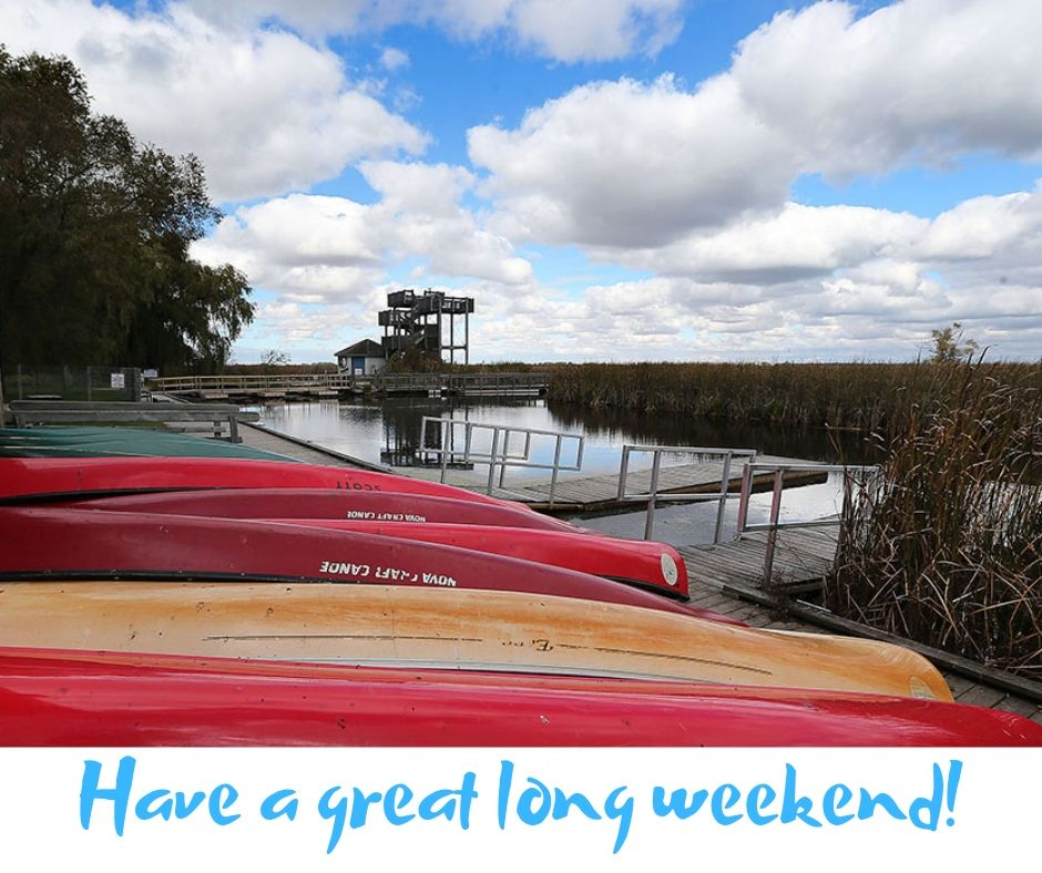 Canoes upside down on a dock beneath a blue sky with white clouds and the words, in blue: 'Have a great long weekend!'