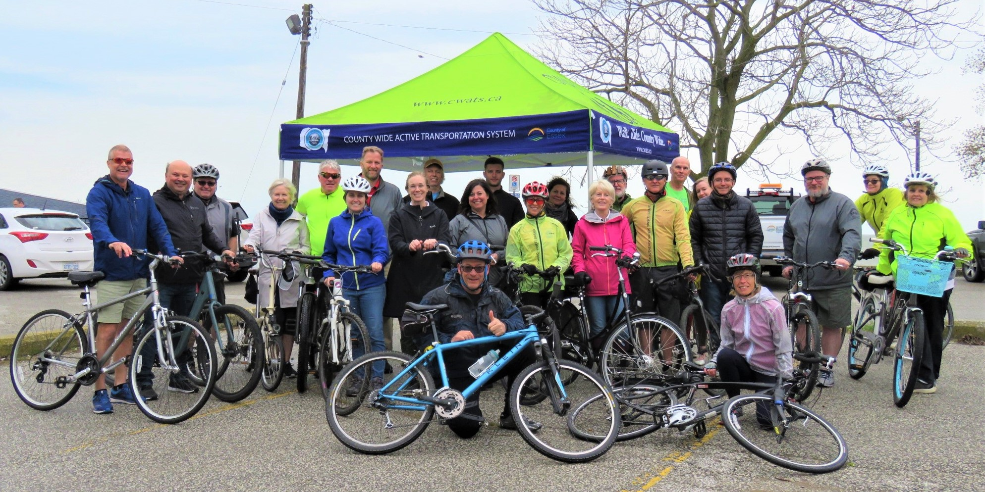 A group of cyclists pose in front of a CWATS tent at Colchester Harbour.