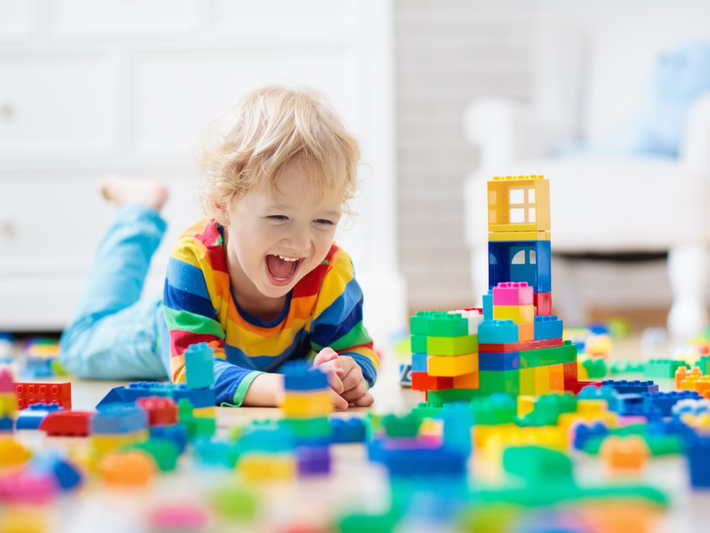 A laughing child plays with colourful blocks.