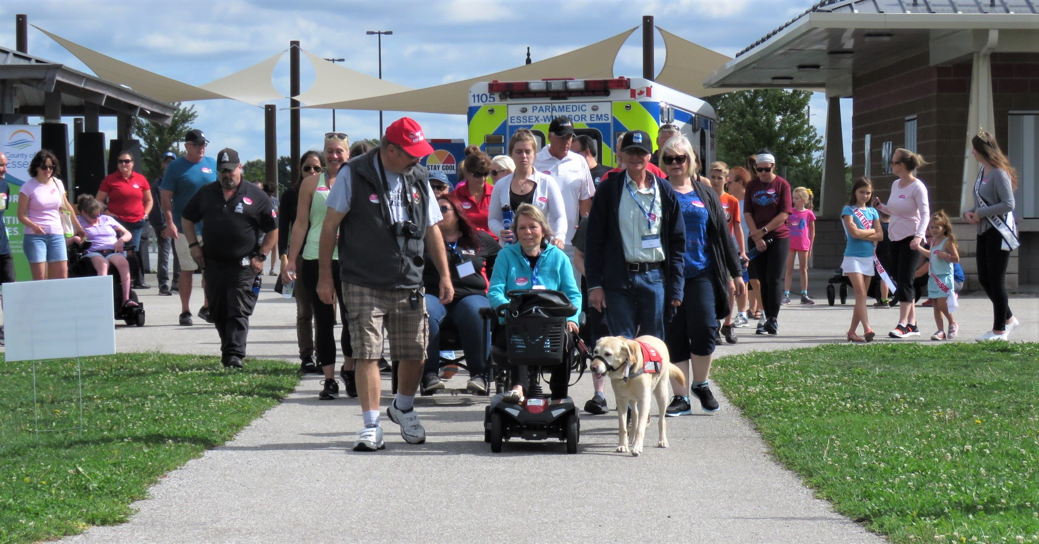A large group follows walk leader Christine Easterbrook at the beginning of the Accessibility Awareness Walk.