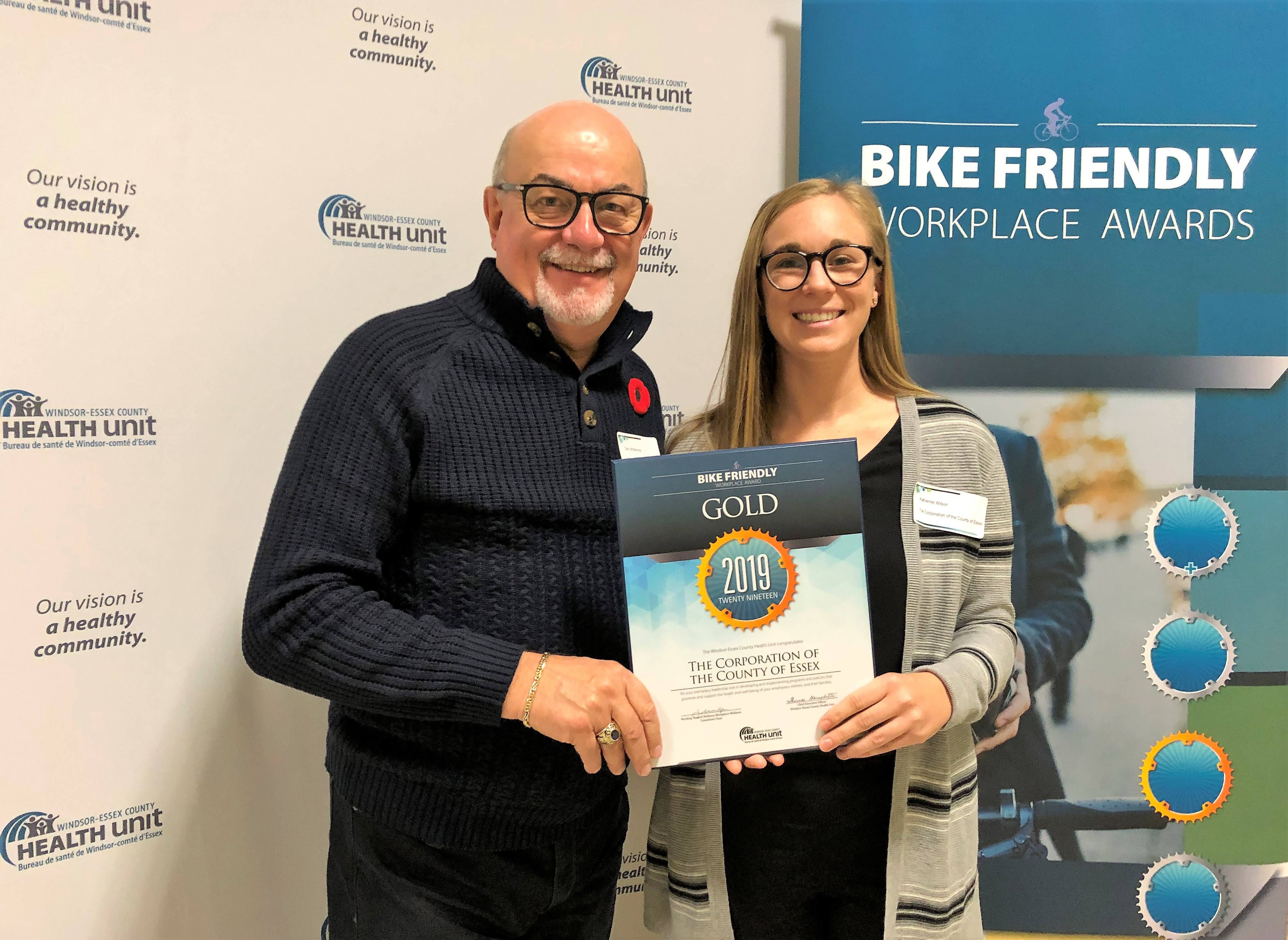 Warden Gary McNamara and Active Transportation Coordinator Katherine Wilson hold a 2019 Gold Bike Friendly Workplace Award