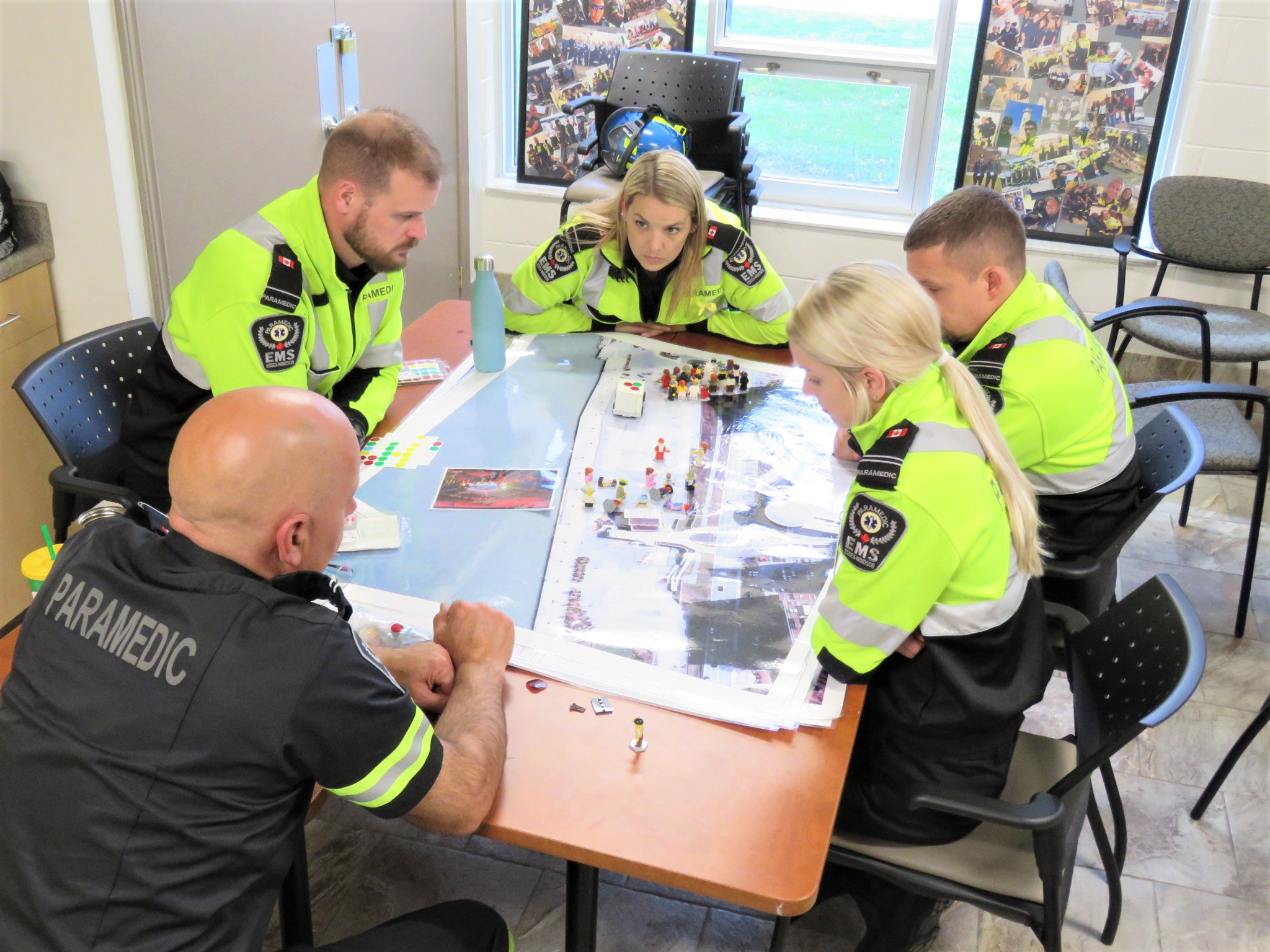 Paramedics gather around a table topped with a map and small Lego pieces.
