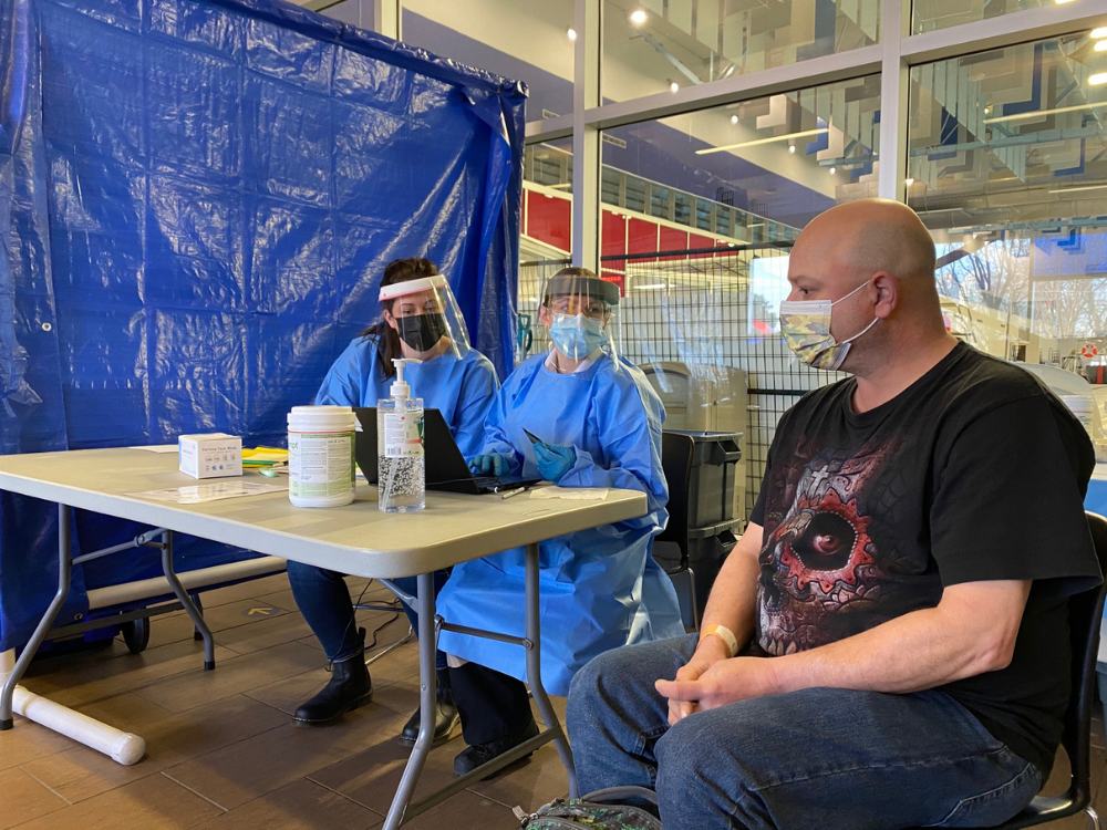 Two Paramedics wearing PPE speak with an individual at the Temporary Emergency Shelter at the Aquatic Centre in Windsor.