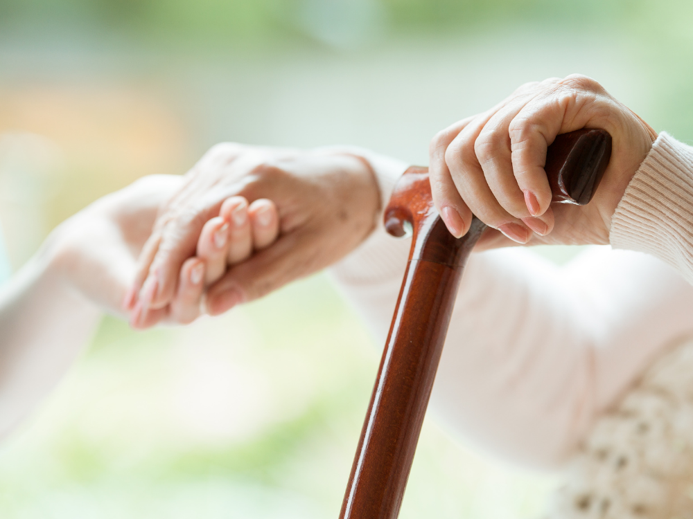 Two people holding hands, one with a cane.