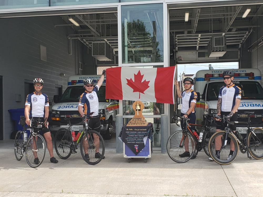 A group of Paramedics on bicycles hold the Canadian flag