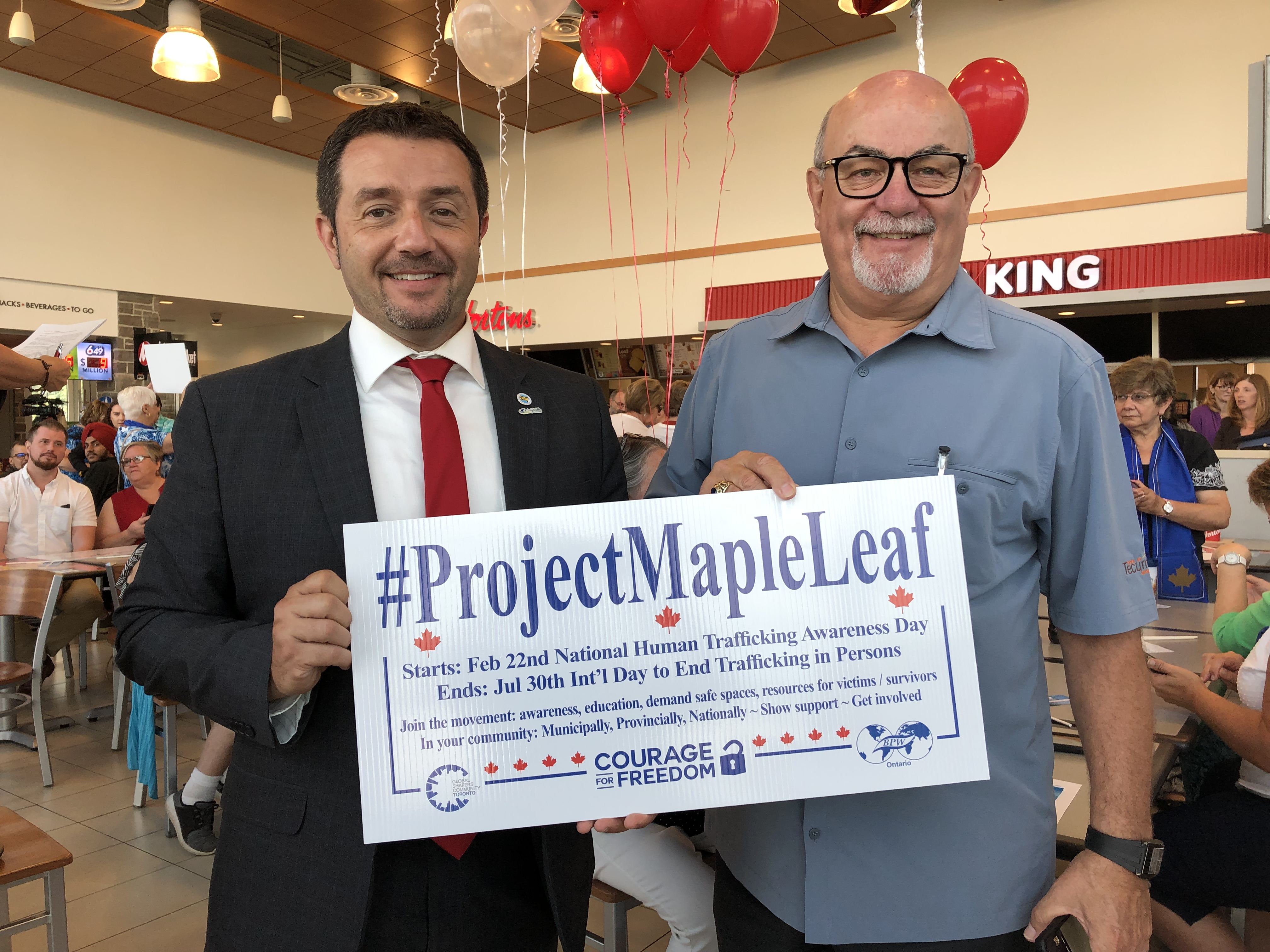 "Nelson Santos and Gary McNamara hold a sign reading ""Project Maple Leaf"""