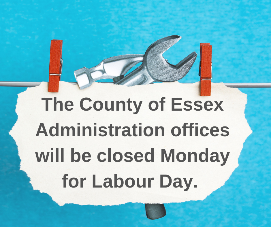 A sign on a clothesline, against a blue sky, reading: The County of Essex Administration Offices will be closed Monday.